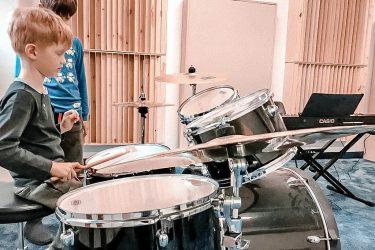 FabLab Pobite Gary, warsztaty muzyczne, chłopiec uczy sięgraćna zestawie perkusyjnym