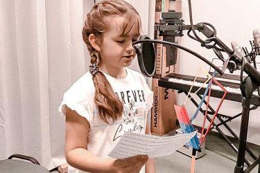 dziewczynka w studio nagraniowym śpiewa do mikrofonu czytając z kartki